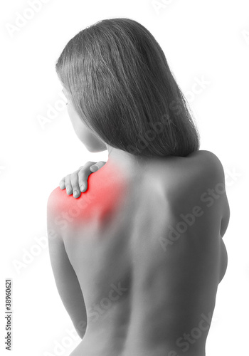 Rear view of a young woman holding her shoulder in pain, isolate