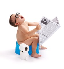 Little boy sitting on potty with newspaper