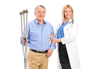 Female doctor or nurse holding a senior patient with crutches
