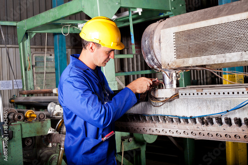 industrial mechanic repairing heavy industry machine