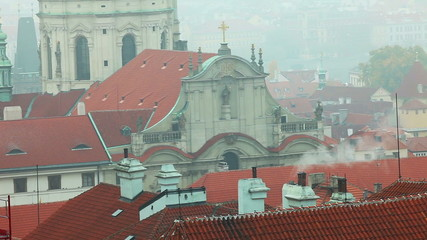 Old Prague roofs at autumn morning with smoke from pipe