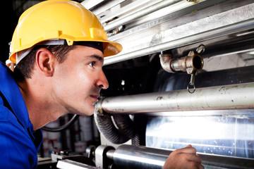 industrial machine operator checking on machine