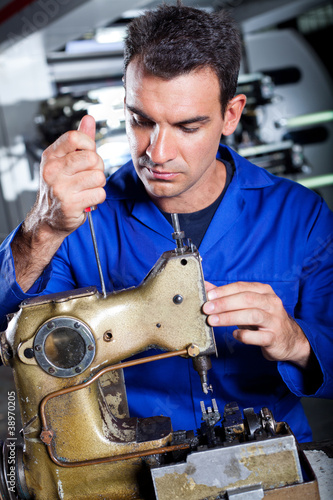 mechanic repairing industrial sewing machine in factory