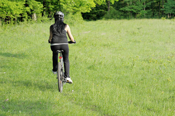 back of an woman riding a bicycle in green environment