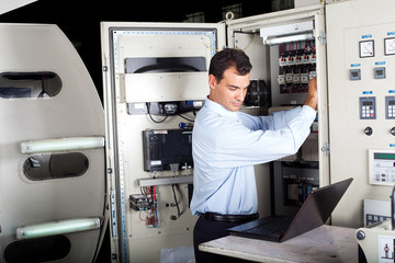 industrial technician repairing modern computerized machine