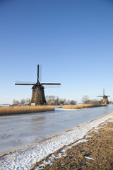 Two windmills in winter time with snow, ice and blue sky