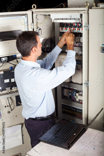 industrial engineer repairing computerized machine