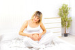 Young beautiful pregnant woman sitting on sofa
