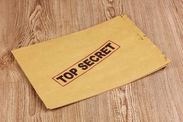 Envelope with top secret stamp on wooden background