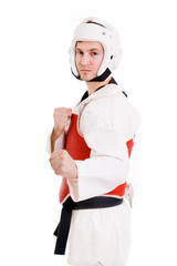 Young man inTaekwondo gear over white background.