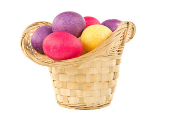 Easter basket with colored eggs iaolted on white