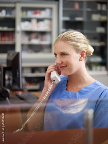 Woman working as nurse in clinic and speaking on telephone