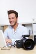 Berufsfotograf mit Kamera und Laptop