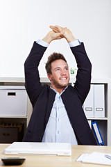 Mann im Büro macht Rückenübungen