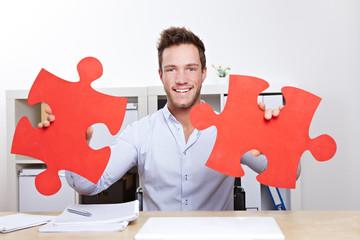 Mann im Büro mit roten Puzzleteilen