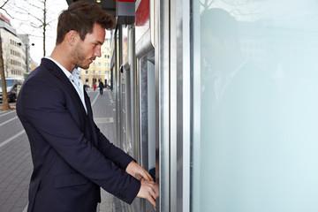Mann am Geldautomat hebt Geld ab