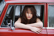 Junges Mädchen in einem roten Oldtimer