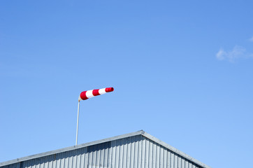 aerodrome red and white windstock and sky