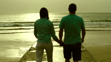 Young happy couple walking at the beach
