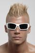 Retrato de un joven punk con anteojos oscuros.