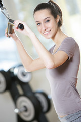 smiling young woman doing on a weight machine at the health club