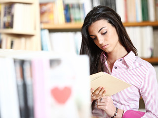 female student reading a book in library