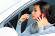 Female driver talking by mobile telephone and doing make-up.