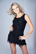 Beautiful young blonde woman wearing black dress over gray