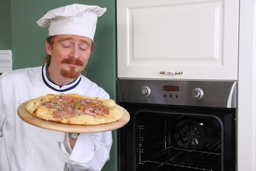 Young chef smelling italian pizza in kitchen