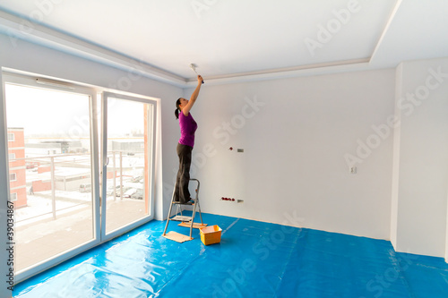 Woman painting ceiling of new apartment