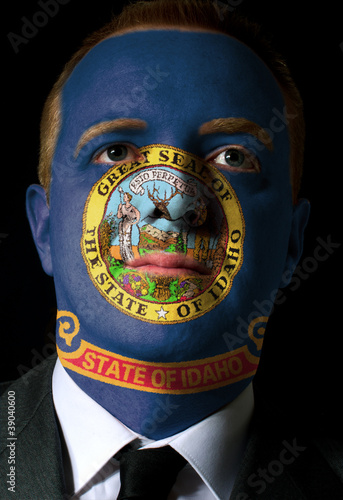 Poster us state of idaho flag painted face of businessman or politician