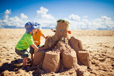 Two boys building large sandcastle on the beach - Fine Art prints