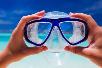 Hand holding snorkel googles against beach
