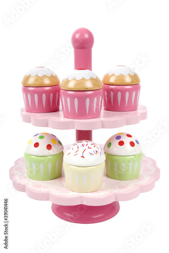 Wooden toy cake stand with cupcakes on white background
