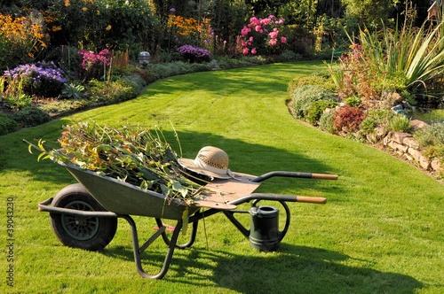 Schubkarre und Gießkanne im herbstlichen Garten