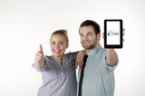 "A young couple showing thumbs up and ""like"" on Tablet PC"