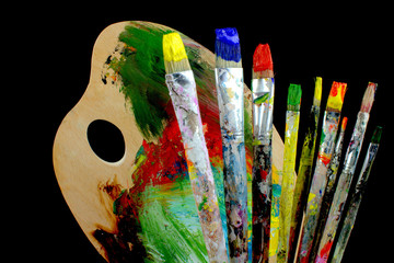 Paintbrushes and palette on black background.