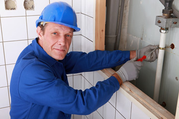 Plumber fixing water supply in bathroom