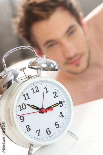 Ringing alarm clock waking up a man