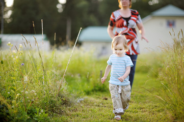 Adorable little girl in a meadow with grandmother