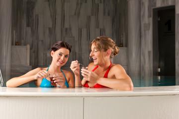 Zwei Freundinnen im Schwimmbad trinken Tee