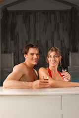 Ein Paar im Schwimmbad trinkt Tee