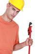 Young bald handyman holding adjustable wrench