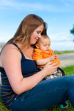 Family - mother and child sitting on a meadow