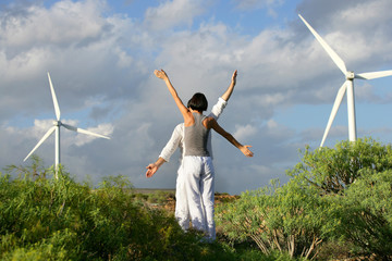 People with arms up near wind turbines