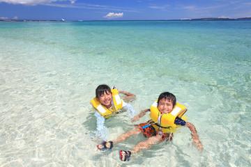 澄んだ海と海水浴を楽しむ笑顔の姉弟