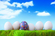 Easter eggs on grass in front of a cloudy sky