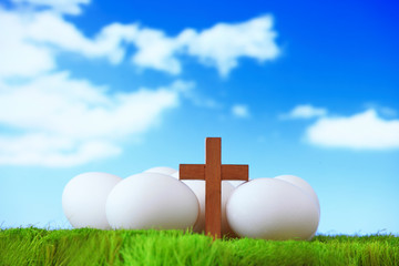 white eggs and wood cross on grass with blue sky