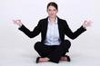 A businesswoman in a lotus position.