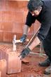 Builder hammering a brick